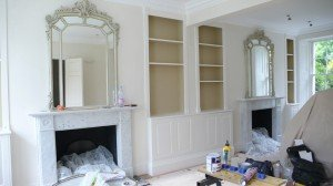 Liivng room starts to come together; pale tan walls and darker brown inside bookshelves
