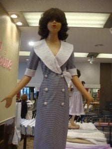 Barbie doll-like dummies model miniature dresses at Paris fabric store