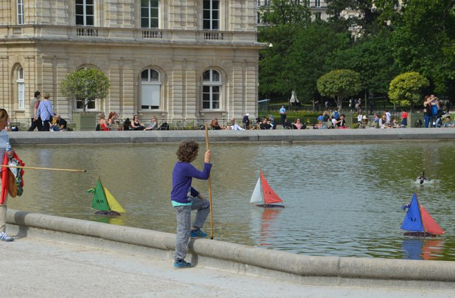 Children playing with rented remote controlled boats at the Jardin du Luxembourg.