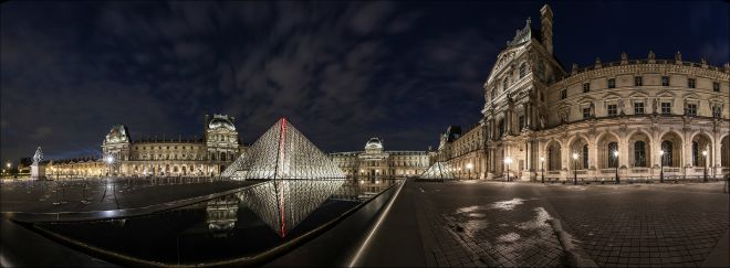 The Louvre museum and I. M. Pei's glass pyramid lit up at night. Image by Adrien Sifre.