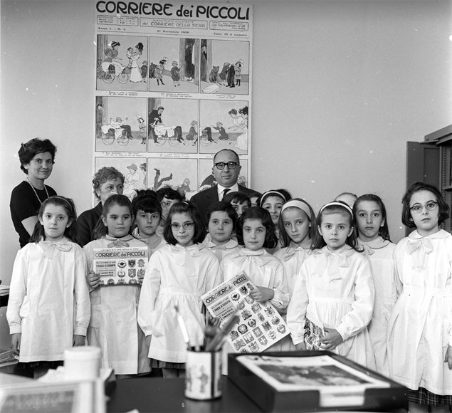 Like this picture, my sisters and I wore white uniforms called Grembiule to school every day. The best children received a red sash — in two years I never got one.