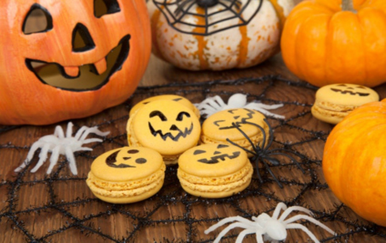 Closeup of Halloween decor with French pumpkin macaroons and assorted pumpkins.