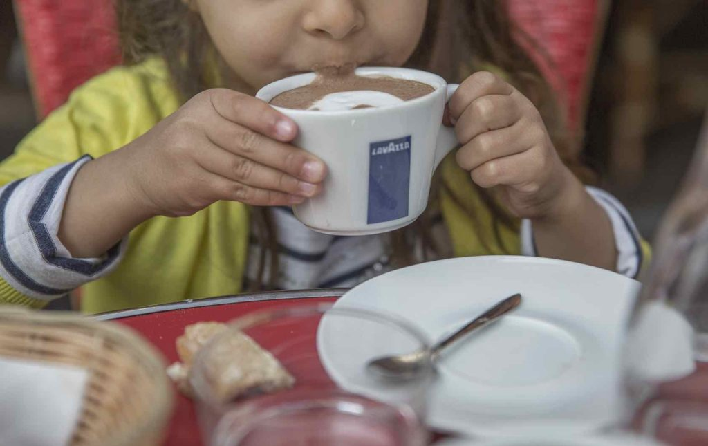 Learn These Essential French Phrases Before Your Trip to Paris by Paris Perfect Child drinking hot chocolate in Paris