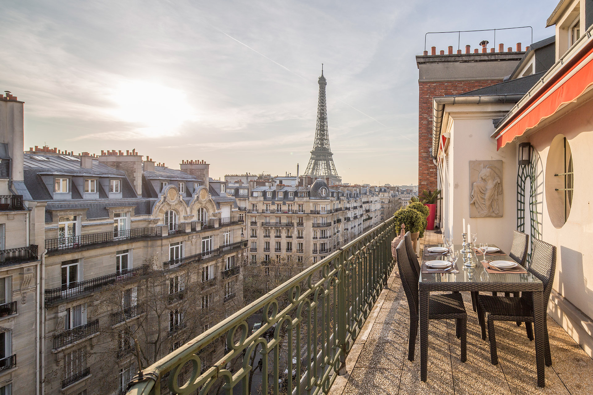 Dining table and chairs on the balcony of the Margaux vacation rental offered by Paris Perfect