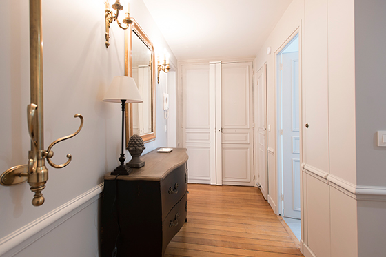 Wall sconces illuminate the hallway of the Monthelie vacation rental offered by Paris Perfect