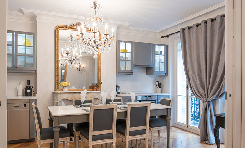Dine underneath a lovely chandelier in the Monthelie vacation rental offered by Paris Perfect