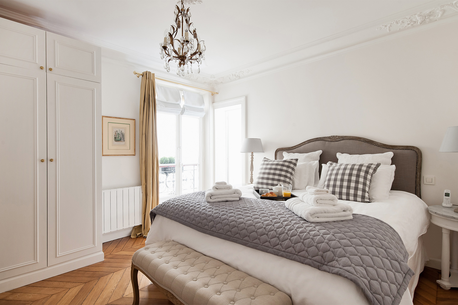 The first bedroom is decorated in soft cream in the Montagny vacation rental offered by Paris Perfect
