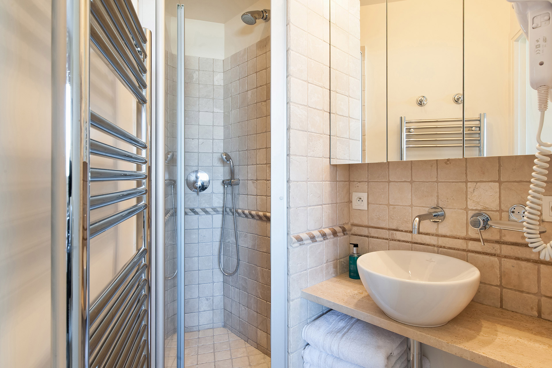 Well-designed bathroom with full-sized shower and sink