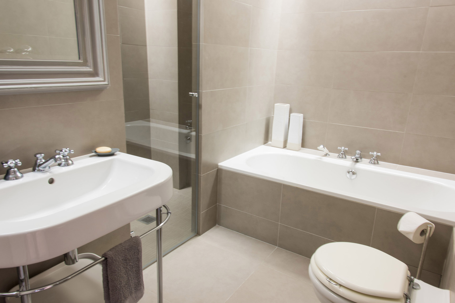 Bathtub, shower, double sink and toilet