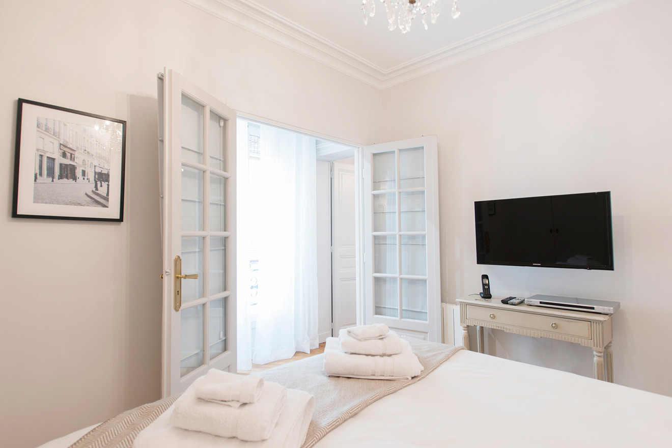 Watch TV in the comfortable extra wide queen bed in the Monthelie vacation rental offered by Paris Perfect