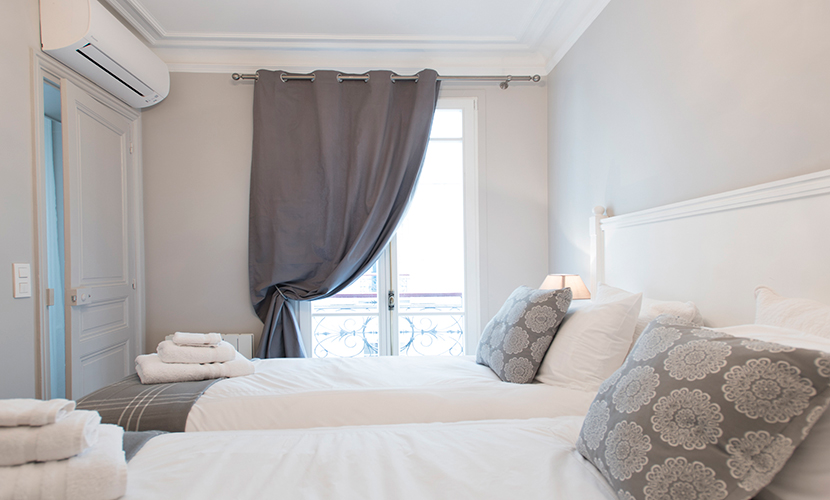 Large grey curtains closed at night in the Monthelie vacation rental offered by Paris Perfect