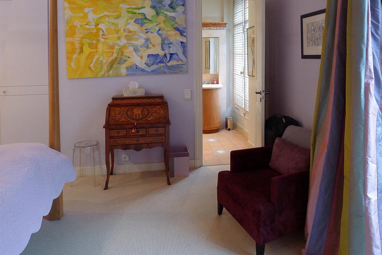 En suite bathroom and elegant antique desk in bedroom