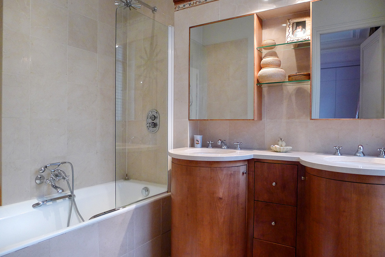 En suite bathroom with bathtub-shower combo and sinks