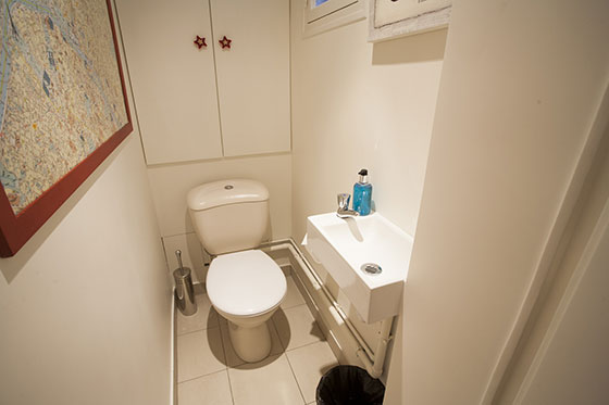 Downstairs half bath with toilet and sink in the Bordeaux vacation rental