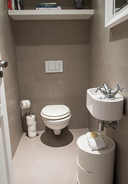 Powder room with toilet and sink located in the hallway