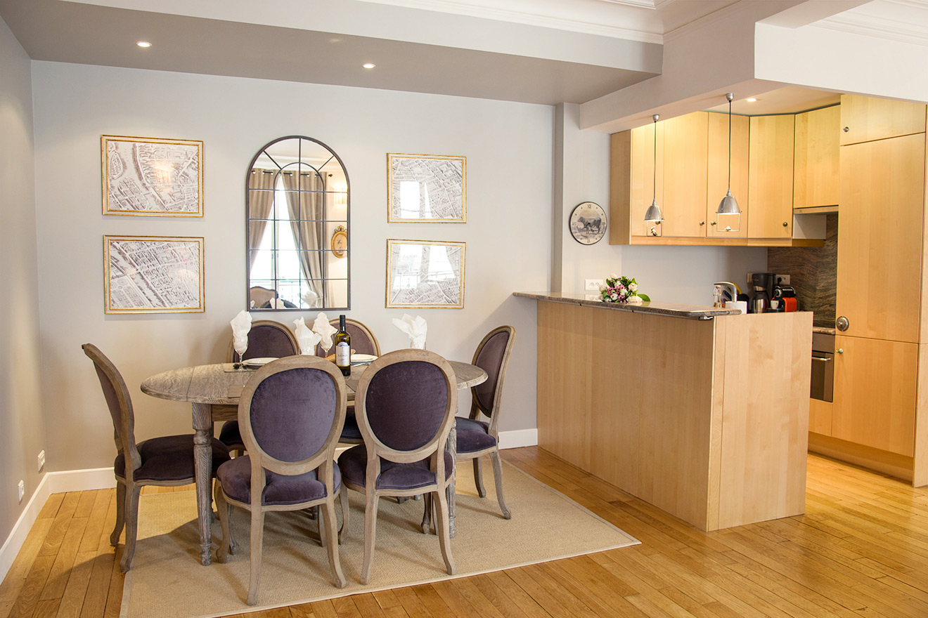 Modern dining table and open kitchen in the Rully vacation rental offered by Paris Perfect