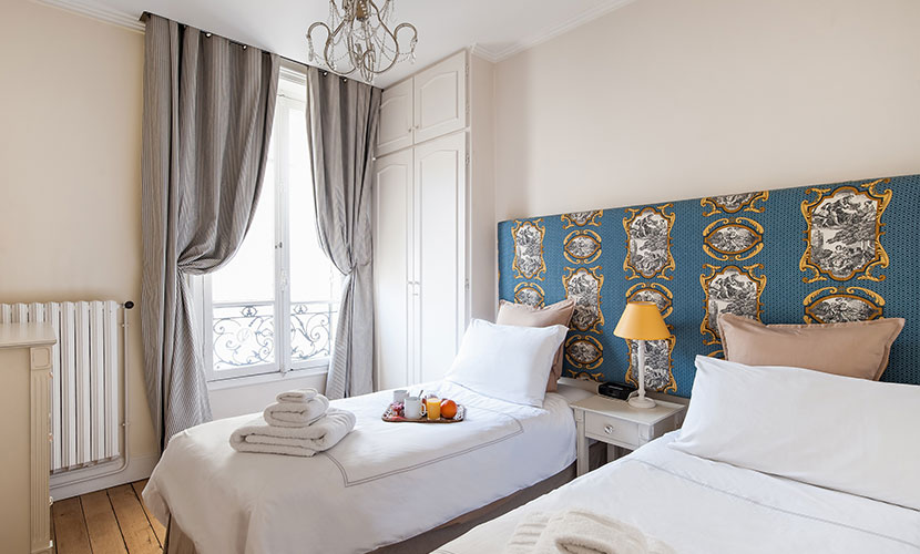 The second bedroom features two single beds in the Vougeot vacation rental offered by Paris Perfect