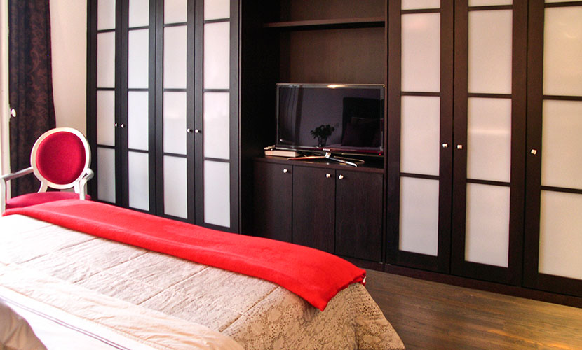 Wall-to-wall closets and flat-screen TV in master bedroom