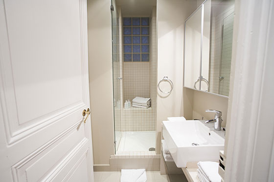 Fully remodeled bathroom with tiled shower and sink in the Chateauneuf vacation rental offered by Paris Perfect