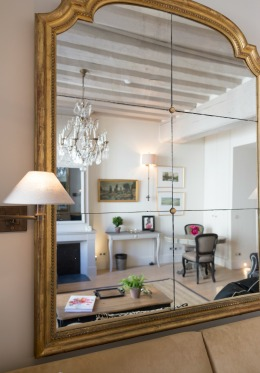 Reflection of living room with TV hidden behind mirror in the Muscat vacation rental offered by Paris Perfect