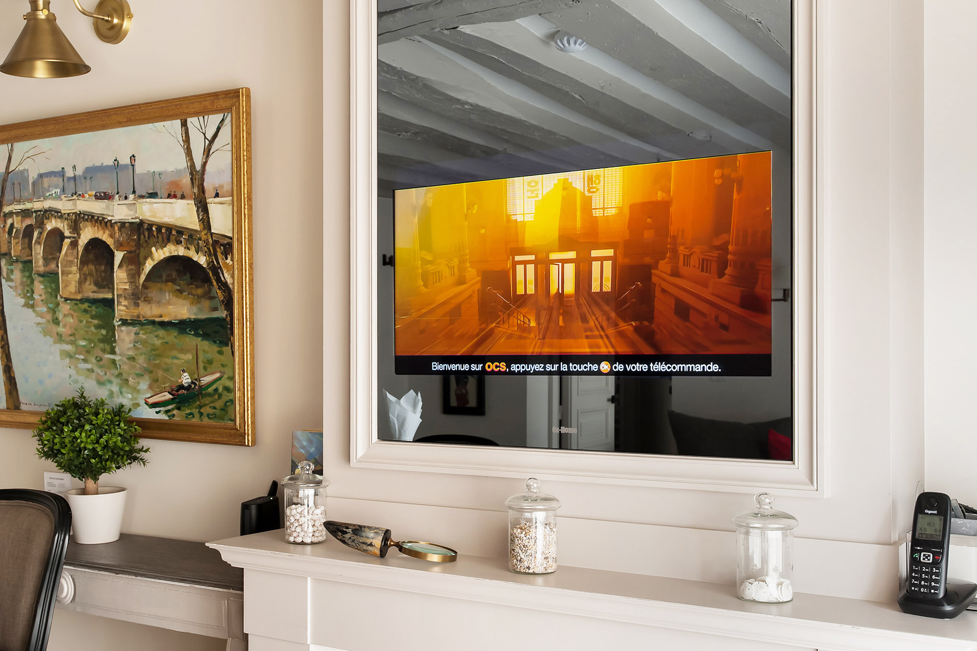 TV in the living room is cleverly hidden behind the mirror in the Anjou vacation rental offered by Paris Perfect