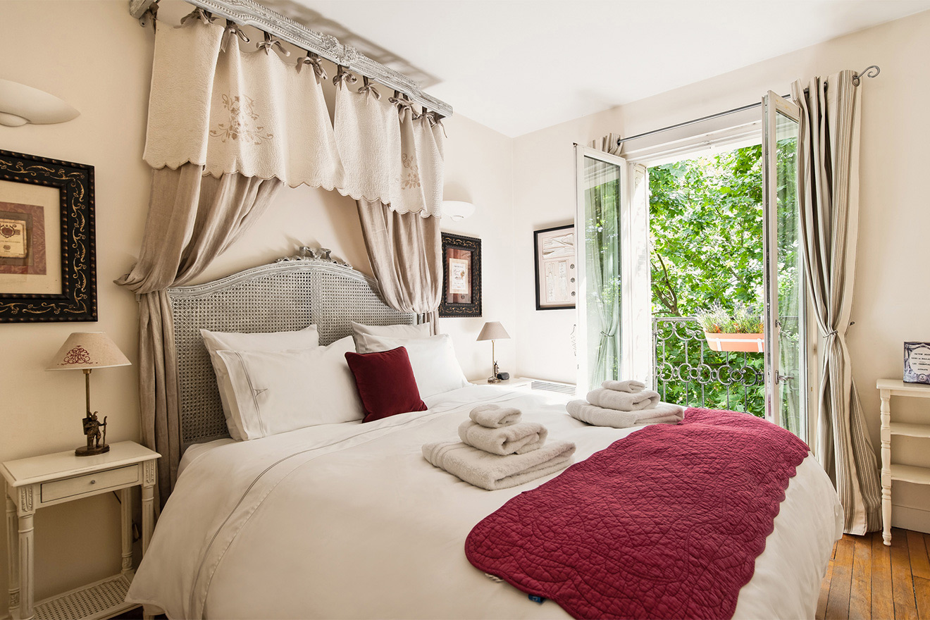 Romantic bedroom with king sized bed in the Champagne vacation rental offered by Paris Perfect