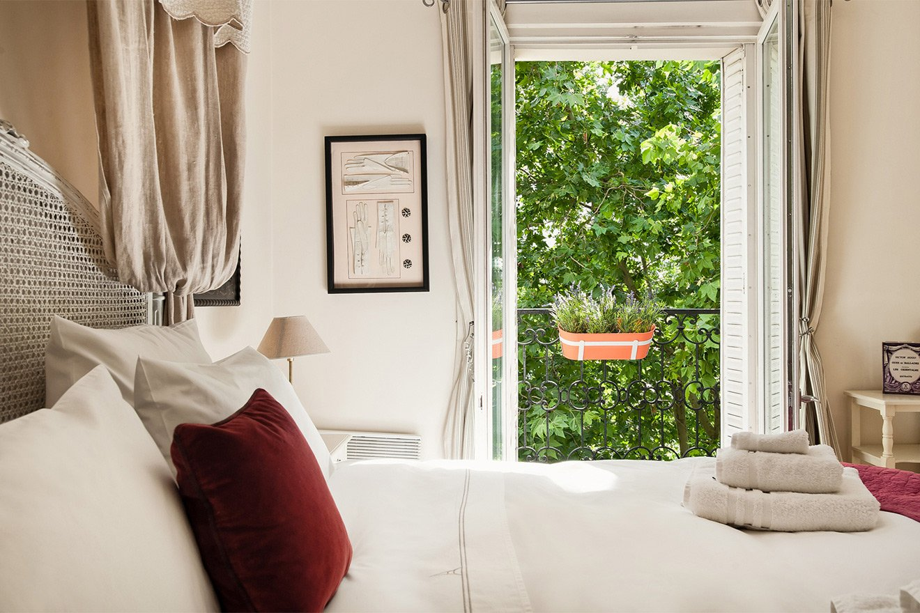 Large windows in the bedroom of the Champagne vacation rental offered by Paris Perfect