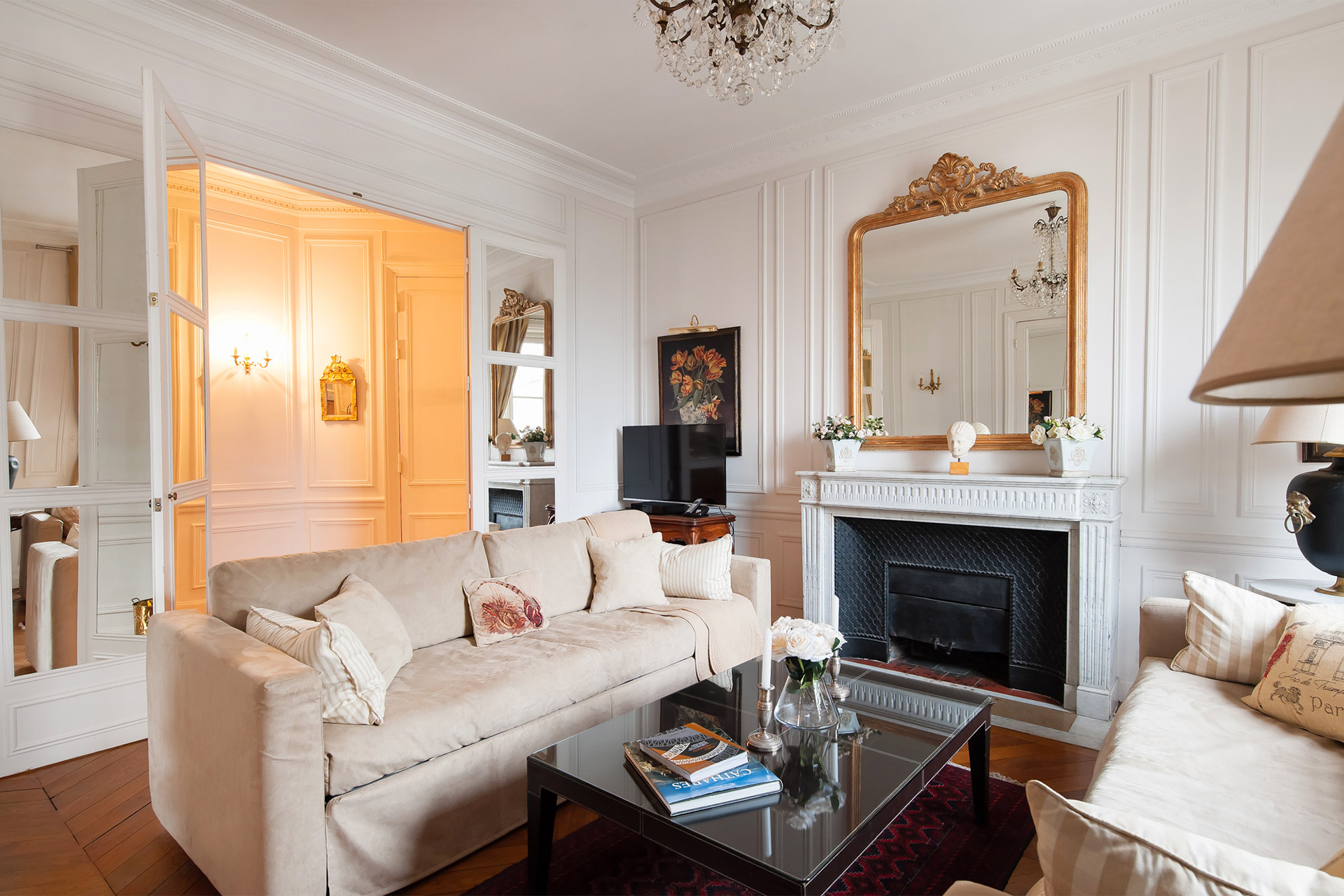 Mirrored French doors divide the living area of the Chateauneuf vacation rental offered by Paris Perfect
