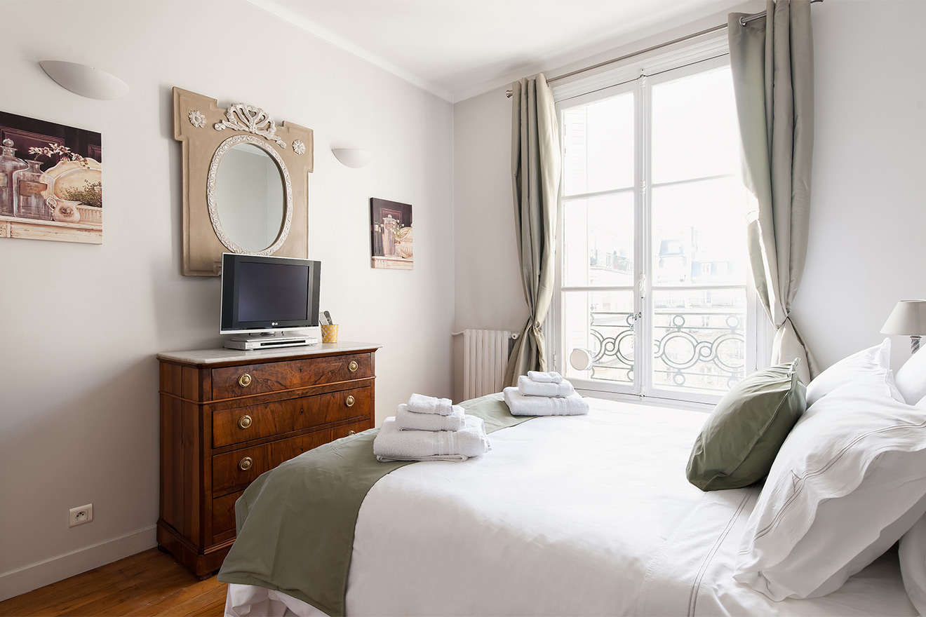 The bedroom overlooks a courtyard in the Cognac vacation rental offered by Paris Perfect