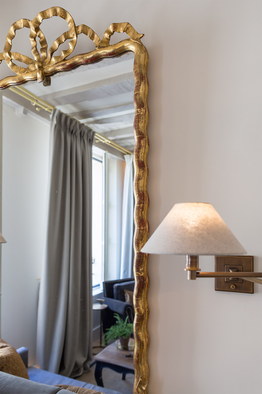 Beautiful golden mirror reflects the living room of the Castillon vacation rental offered by Paris Perfect