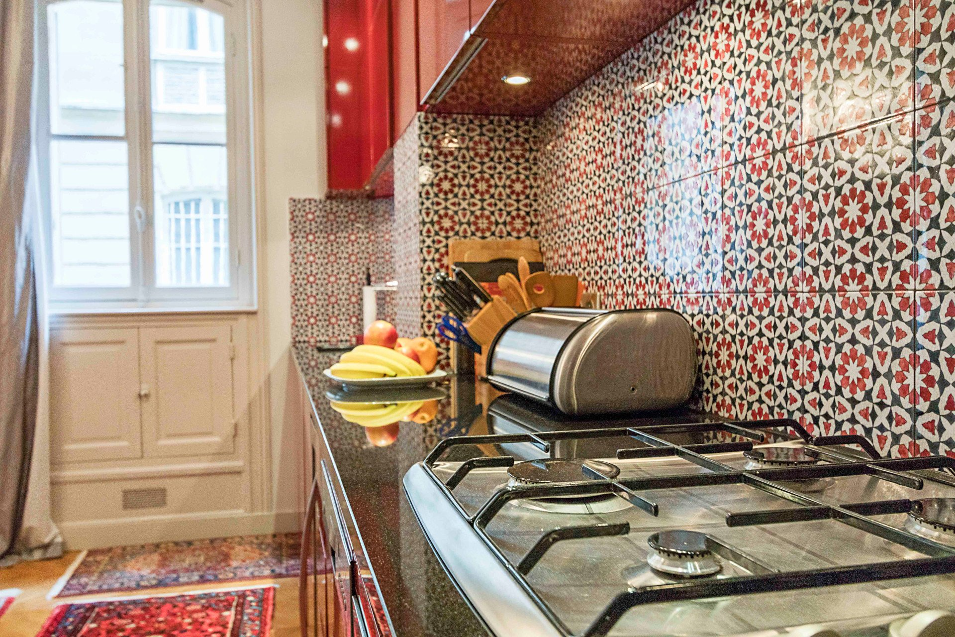 Check out the beautiful tiling on the kitchen walls in the Roannaise vacation rental by Paris Perfect