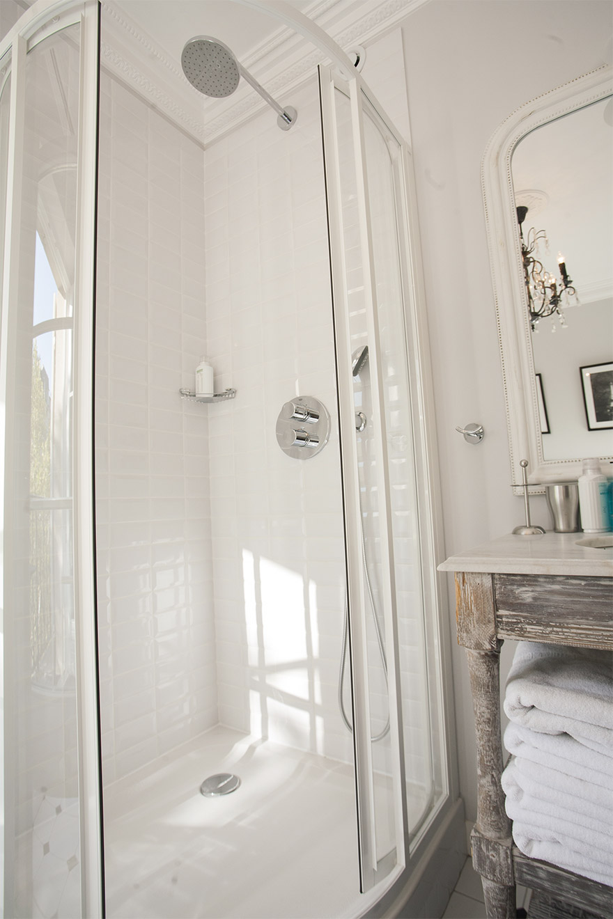 Glass-enclosed shower in the mirror in the Chambertin vacation rental offered by Paris Perfect