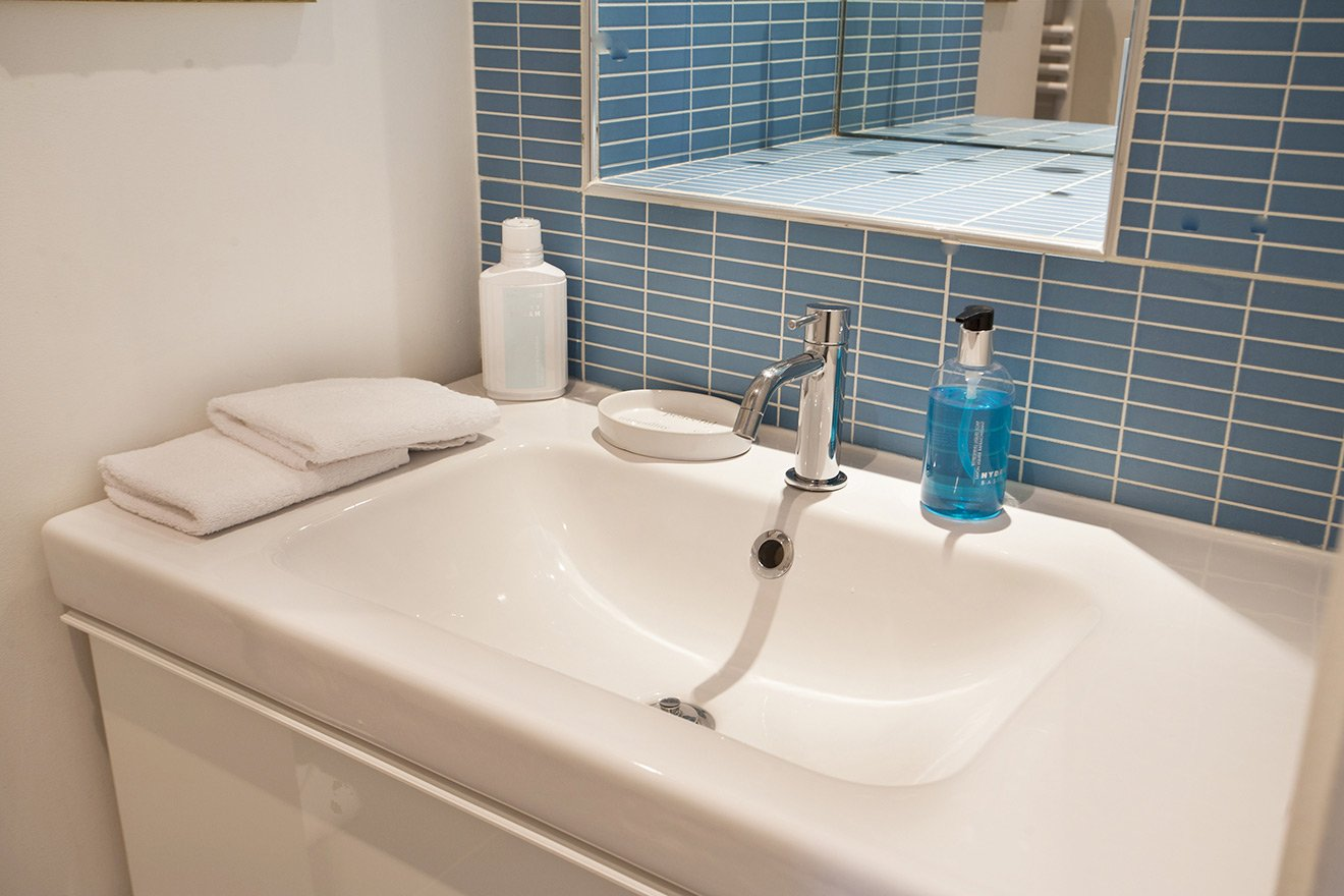 Niche for towels and shelf located above sink in bathroom