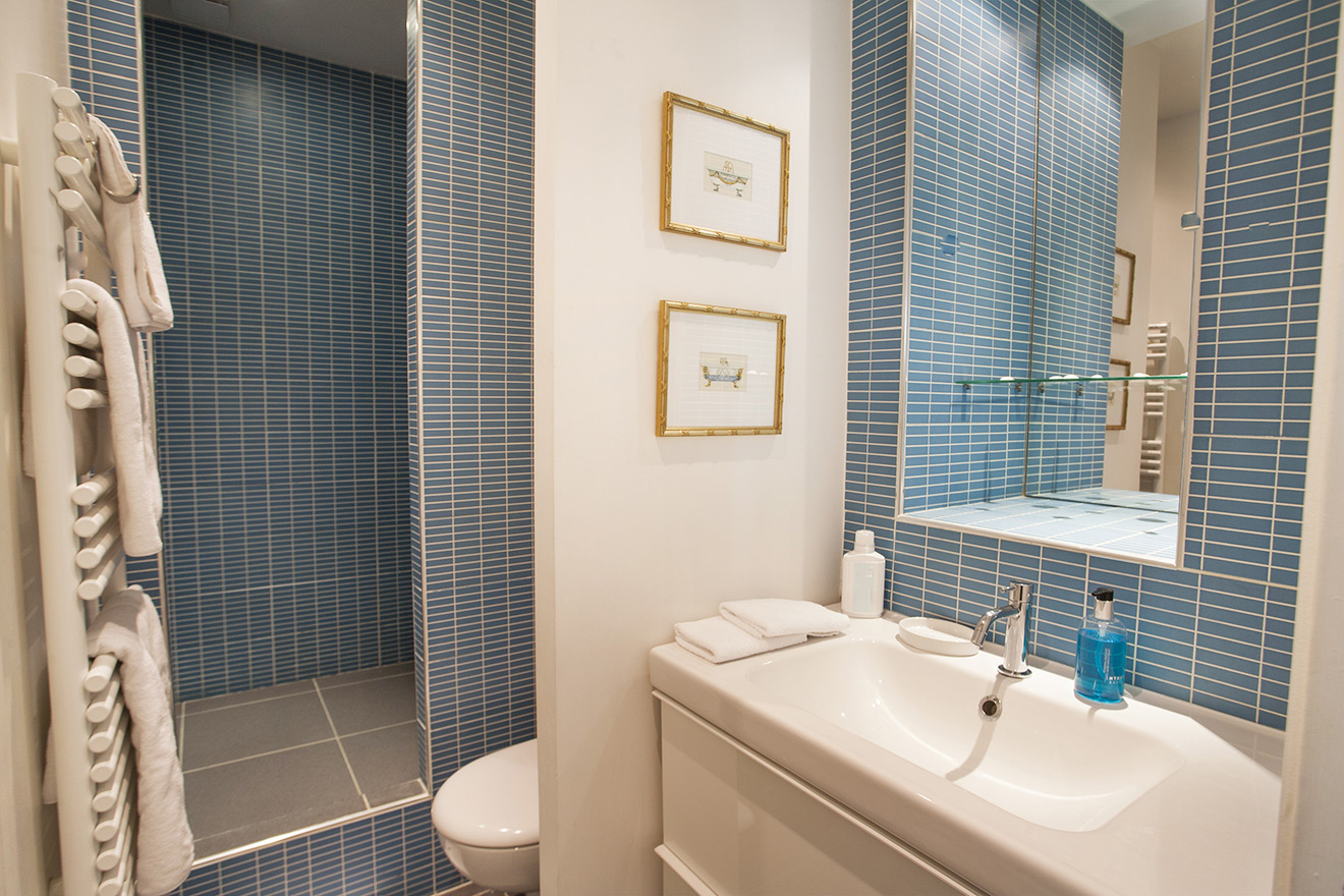 Beautiful bathroom with shower, toilet, sink and heated towel rack