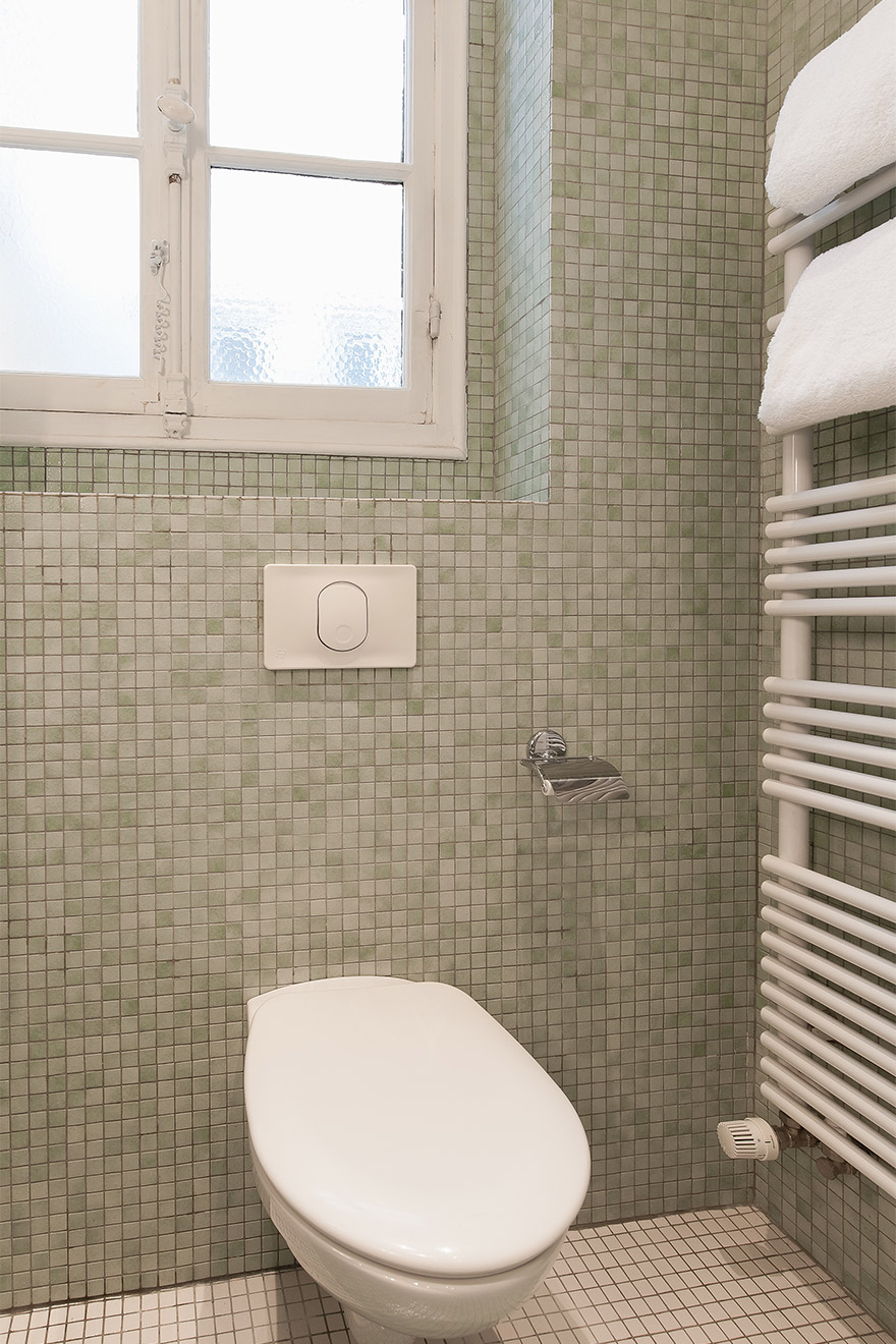 Toilet and heated towel racks in the first bathroom of the Mâcon vacation rental offered by Paris Perfect