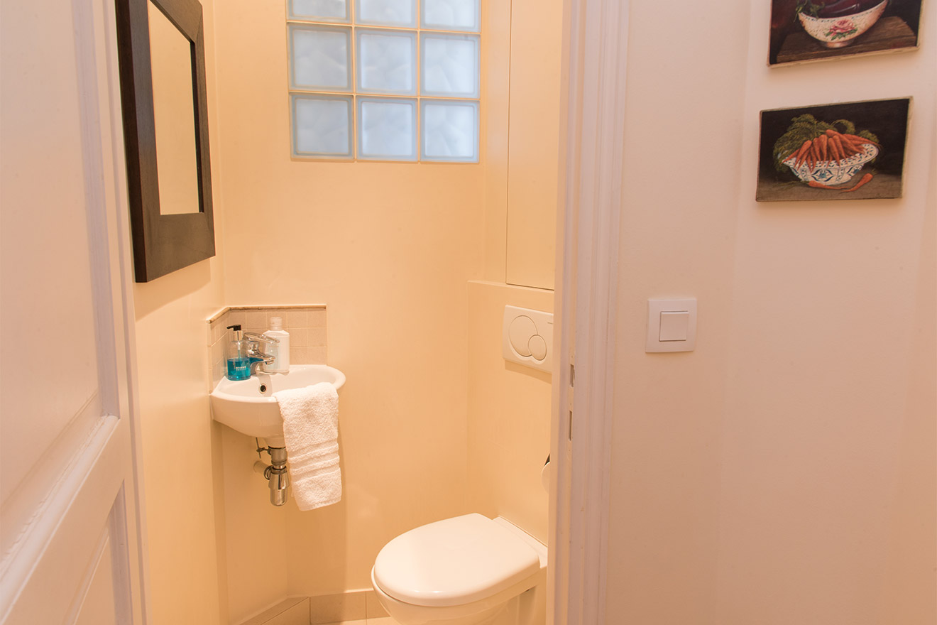 Separate powder room with toilet and sink in the Chateau Latour vacation rental offered by Paris Perfect