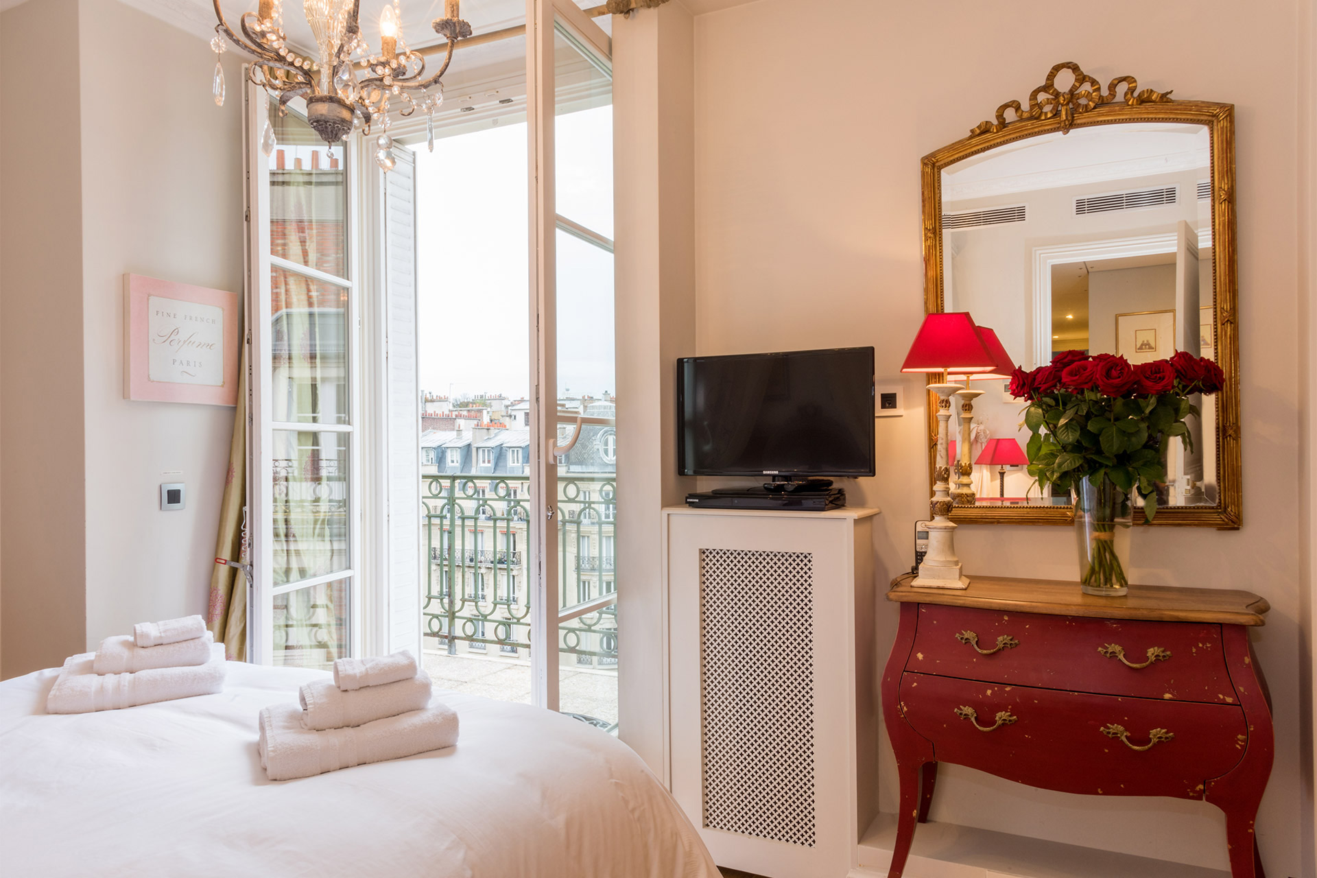 Antique red chest of drawers in the bedroom of the Margaux vacation rental offered by Paris Perfect
