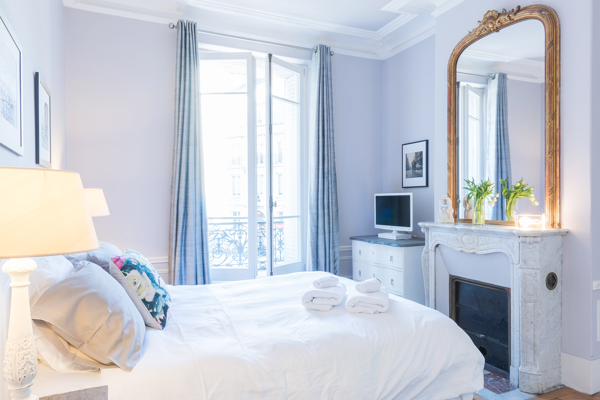 The king size bed is a cozy spot to read in bed in the Maubert vacation rental offered by Paris Perfect