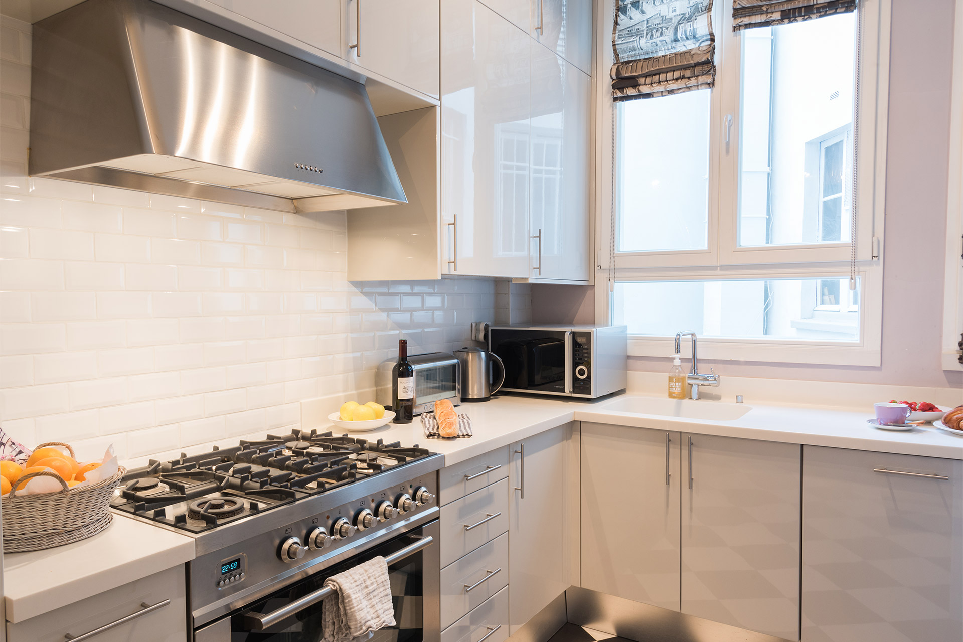 Kitchen with stylish black and white check flooring in the Maubert vacation rental offered by Paris Perfect