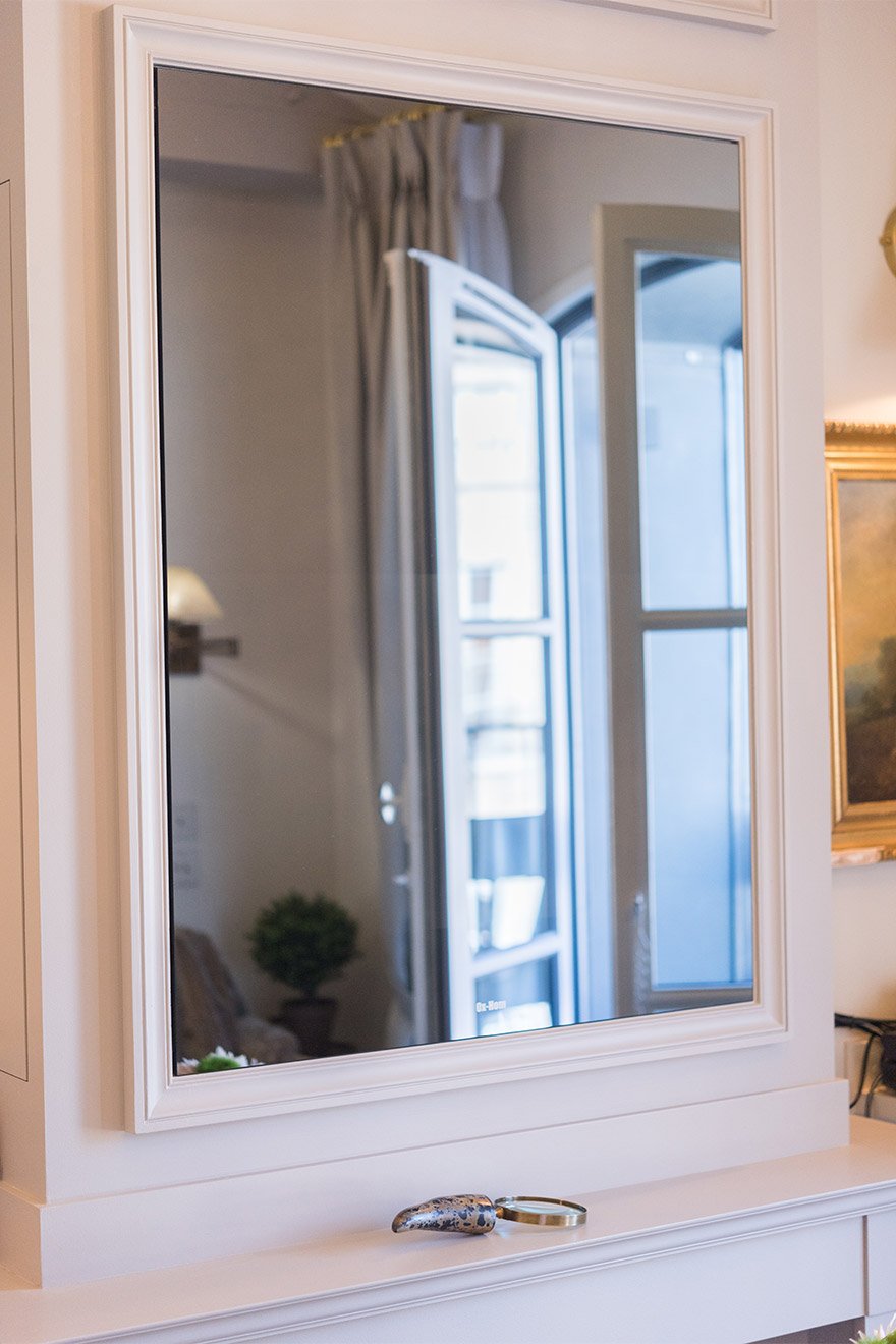 Mirror above the fireplace masks the TV in the Monbazillac vacation rental offered by Paris Perfect