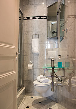 First bathroom with glass-enclosed shower, toilet and sink