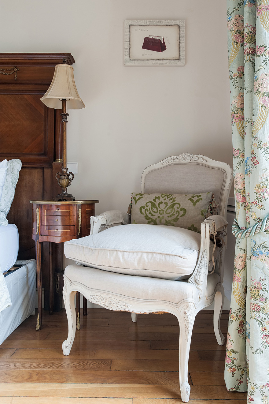 Antique style chair next to bed in the Saint Amour vacation rental offered by Paris Perfect