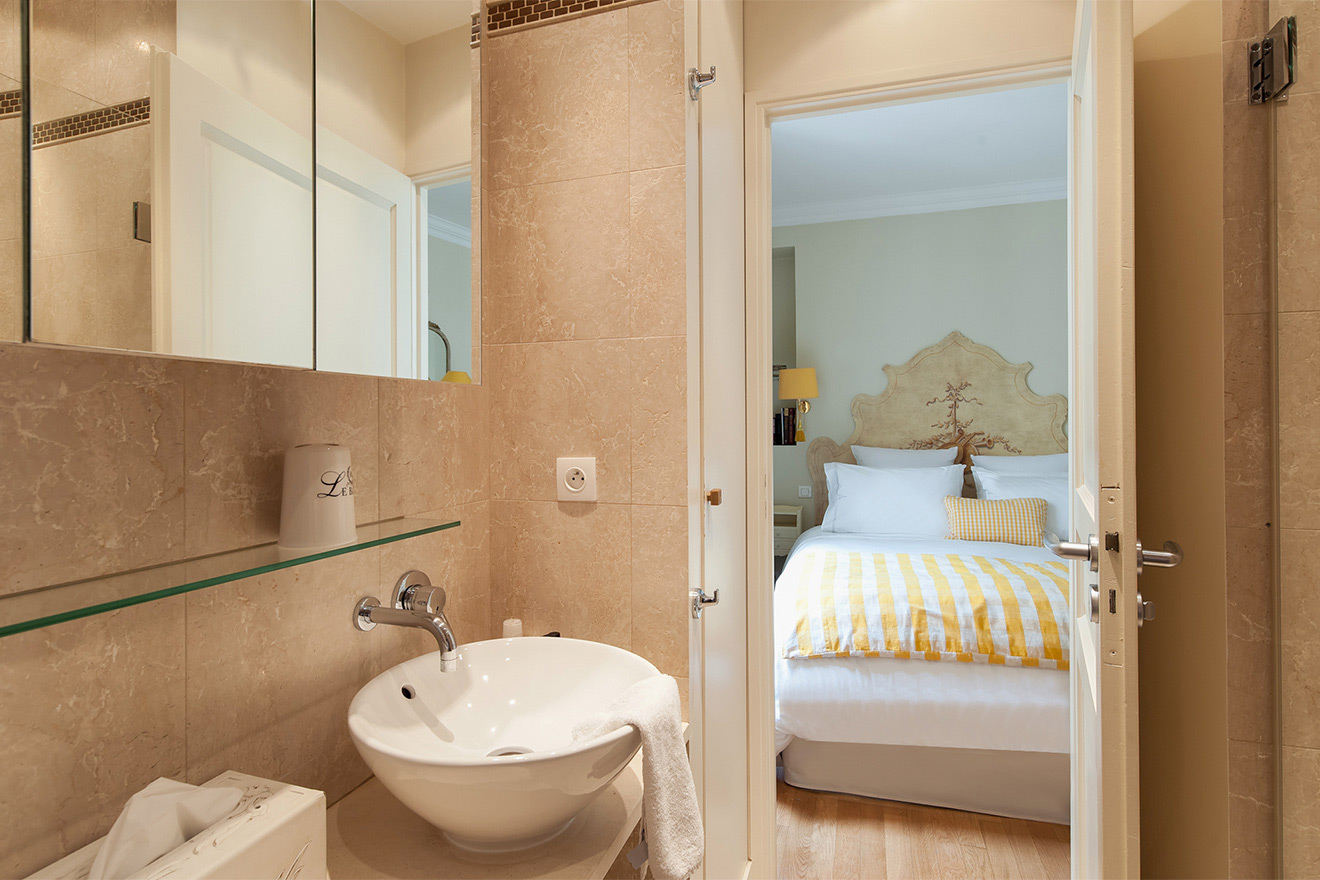 Bathroom tiled in Travertine marble in the Saint Julien vacation rental offered by Paris Perfect
