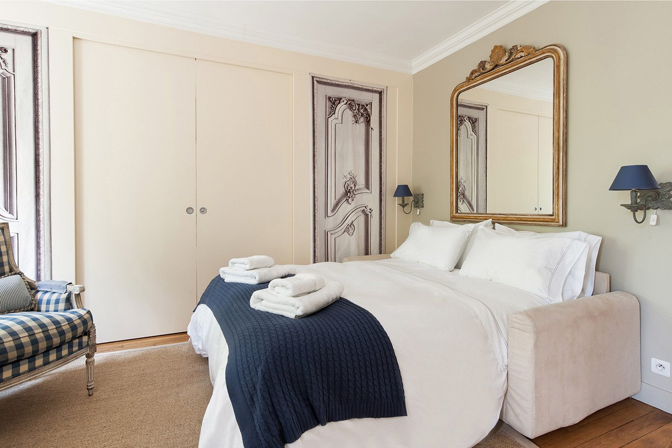 Sliding doors provide privacy for this sleeping area of the Saint Julien vacation rental offered by Paris Perfect