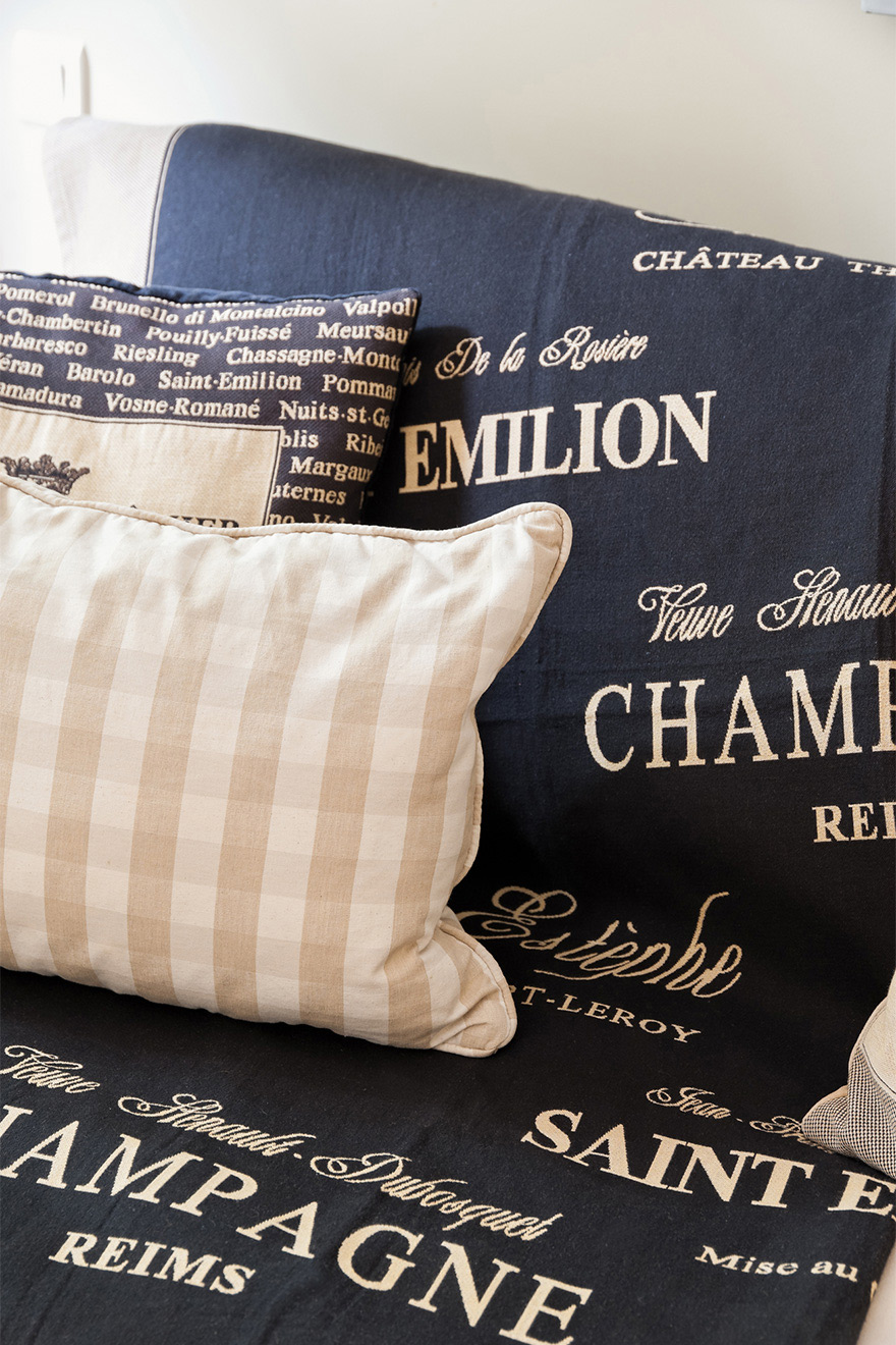 Elegant cushions and throw rug with French wine names in the Saint Julien vacation rental offered by Paris Perfect