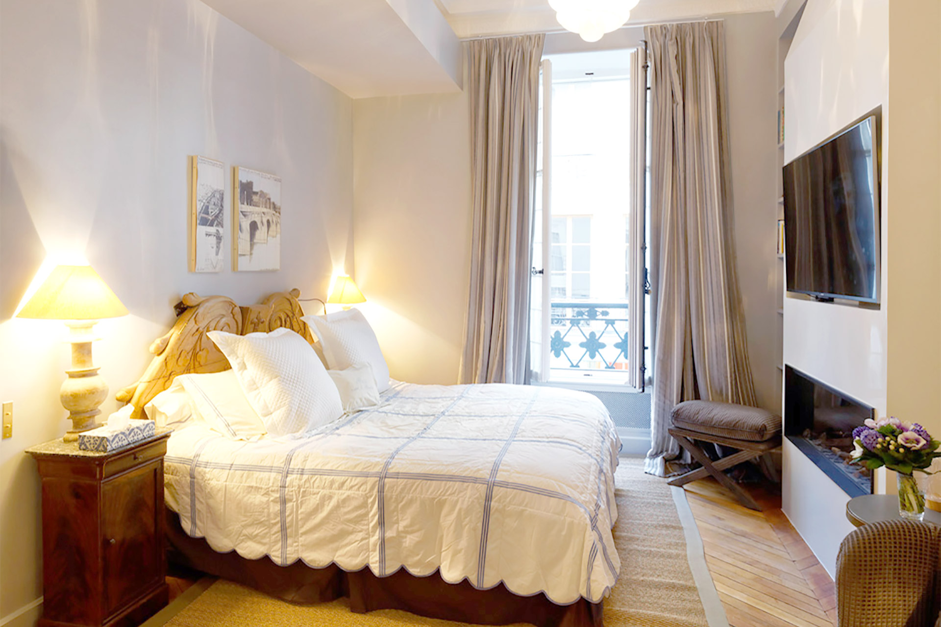 Spacious bedroom one with a fireplace, TV and large en suite bathroom in the Bailly Paris vacation rental