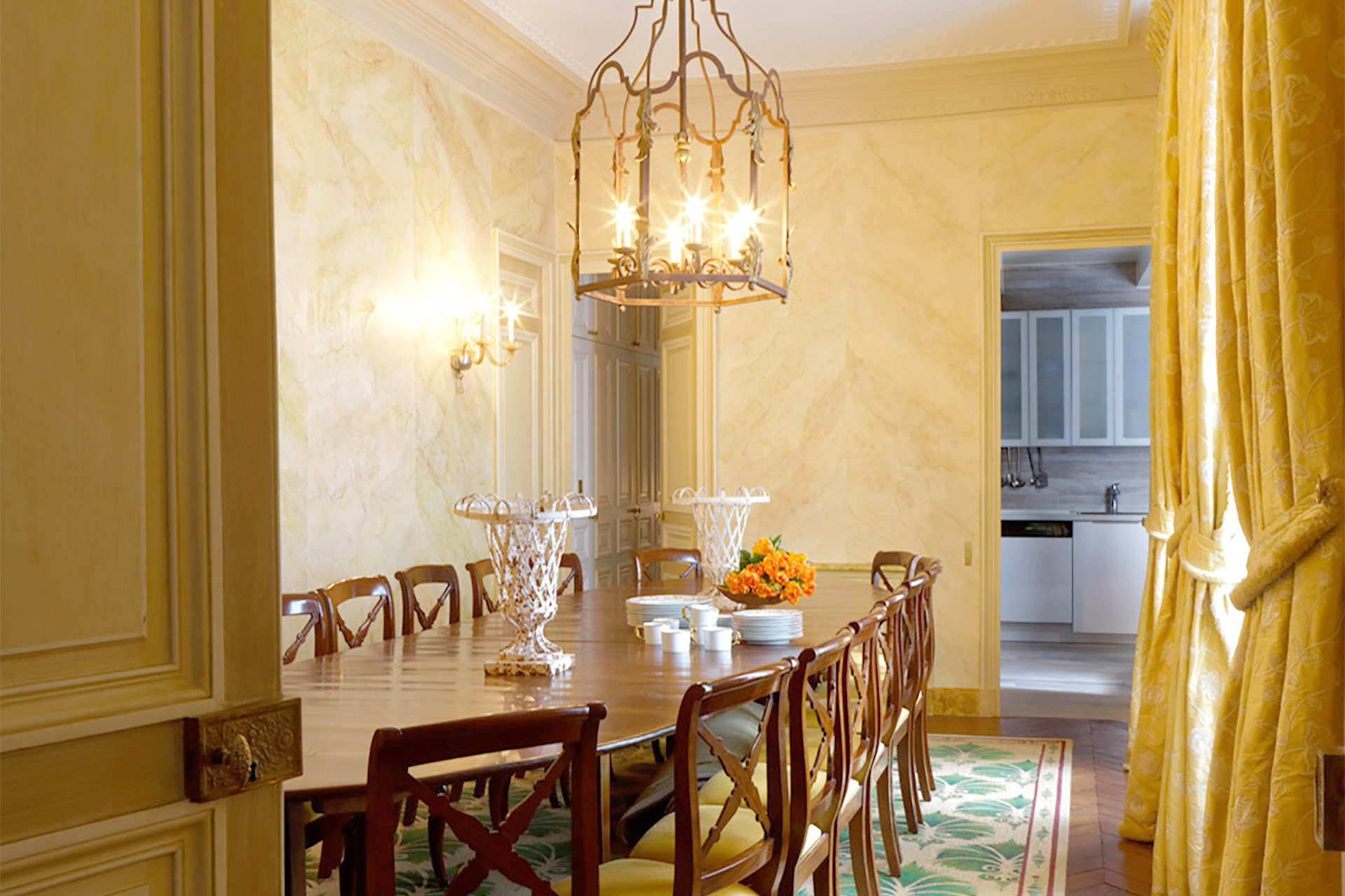 Sunlight streams through the large French windows in the dining room in the Bailly Paris vacation rental