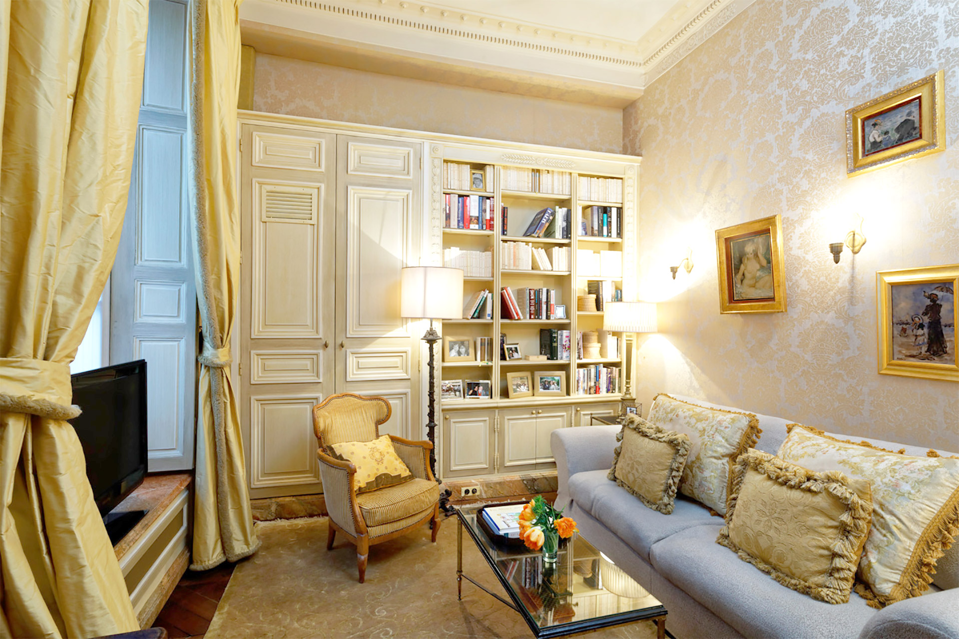 Second living room in the Bailly Paris apartment with a TV and built-in bookcase