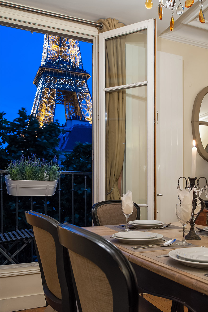 Eiffel Tower view from the dining table at night in the Bergerac vacation rental offered by Paris Perfect