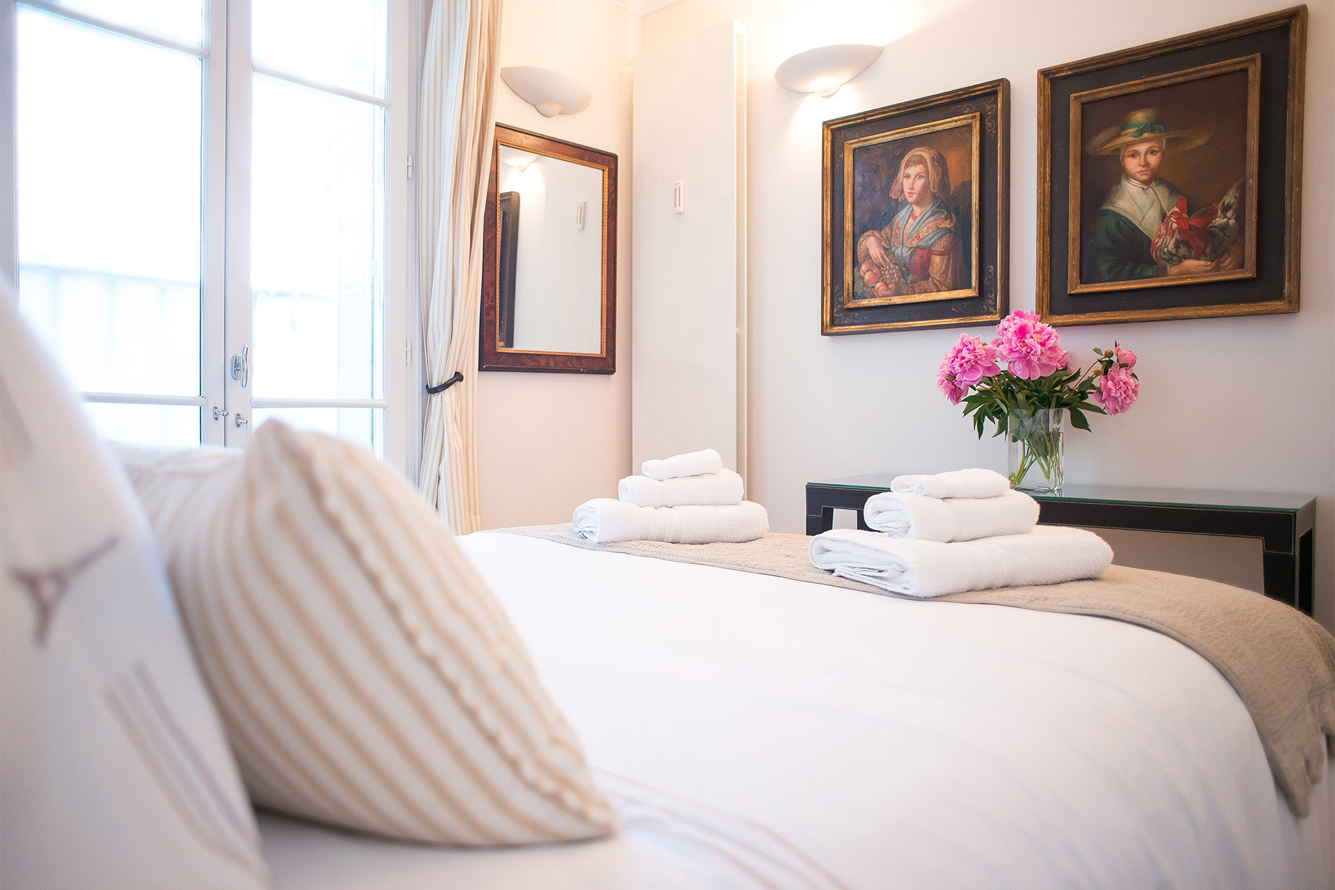 Antique pictures hang on the bedroom wall of the Bergerac vacation rental offered by Paris Perfect